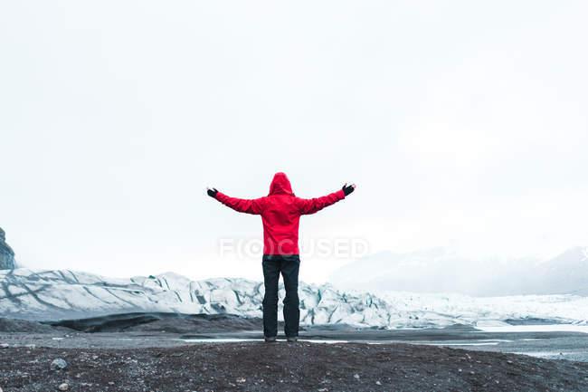 Uomo in abiti caldi in piedi nel paesaggio innevato — Foto stock
