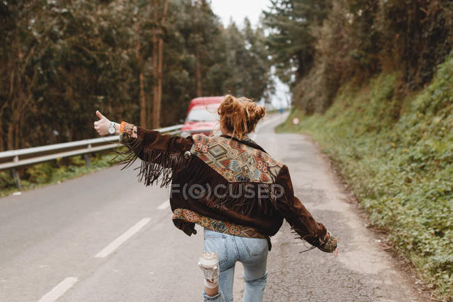 Woman hitchhiking in woods — Stockfoto