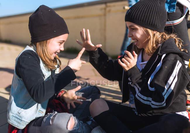 Модные бунтарки, сидящие на тротуаре под солнцем и играющие в игры камень-ножницы-бумага, веселятся. — стоковое фото