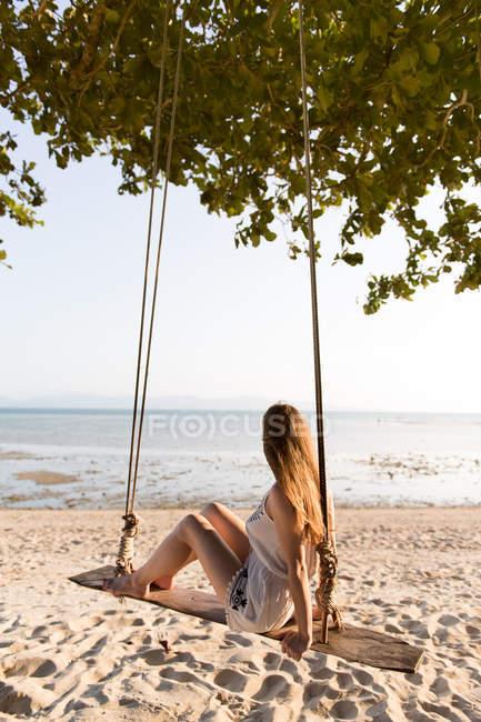 Femme assise sur des balançoires sur la plage — Photo de stock