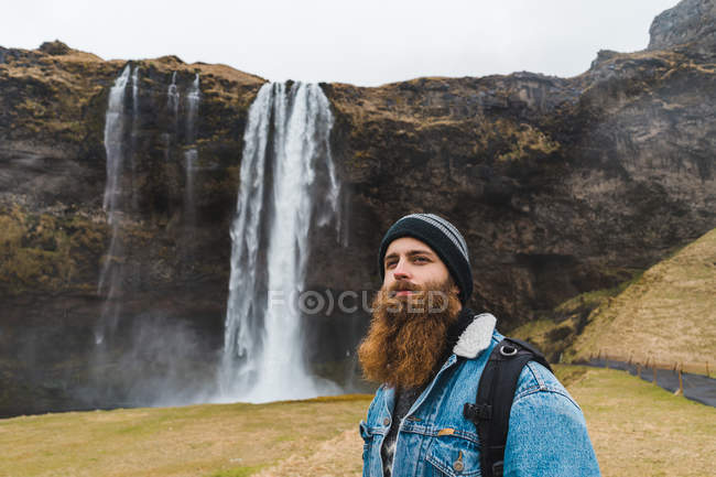 Людина, що стоїть перед водоспад — стокове фото