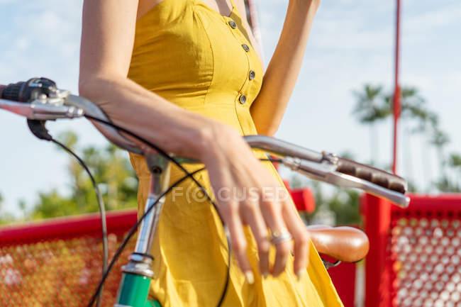 Жінка в літній одяг, спираючись на велосипеді — стокове фото