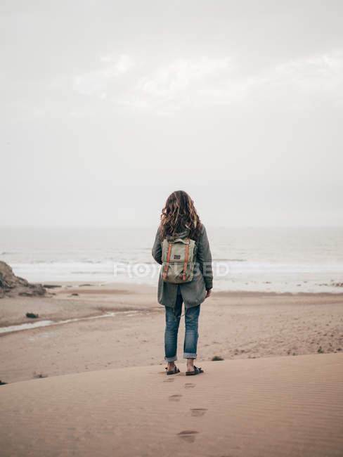 Femme avec sac à dos debout à l'océan — Photo de stock