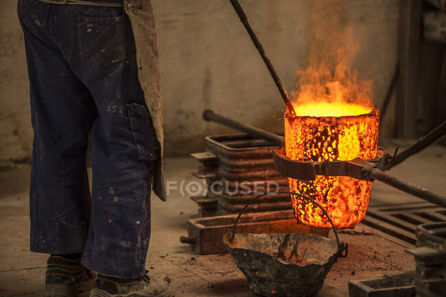 Crop view of male in work clothes standing and preventing coals in oven with burning fire — Stock Photo