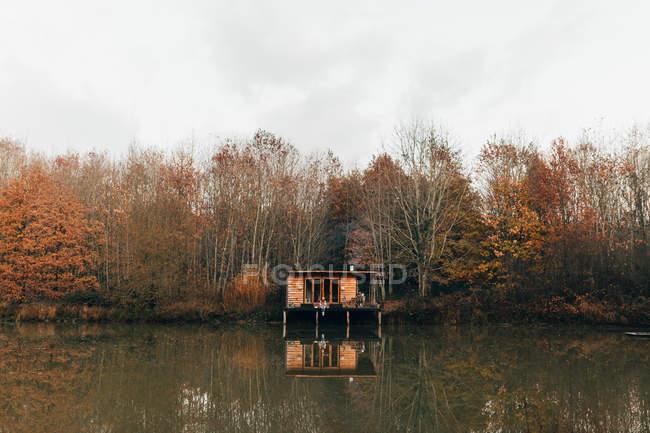 Mujer sentada en el porche en el estanque - foto de stock
