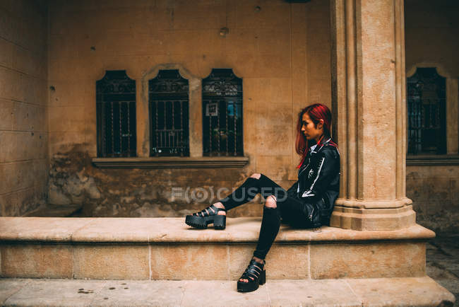 Woman sitting on old stone gallery — Stock Photo