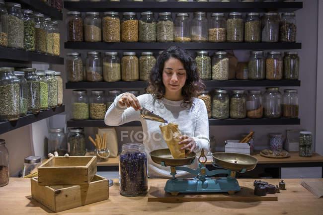 Женщина кладет специи в сумку — стоковое фото