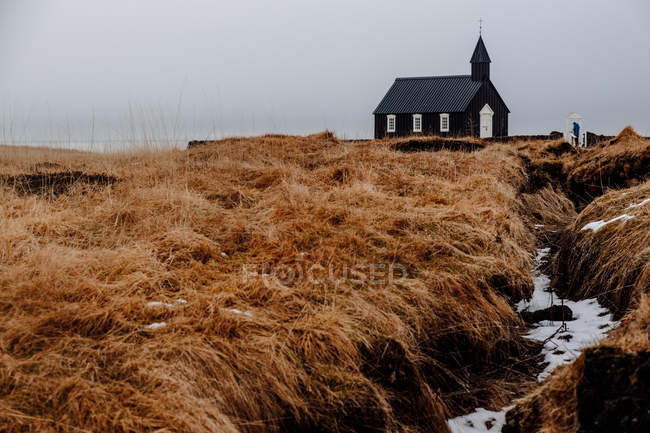Small church on dry meadow — Stock Photo