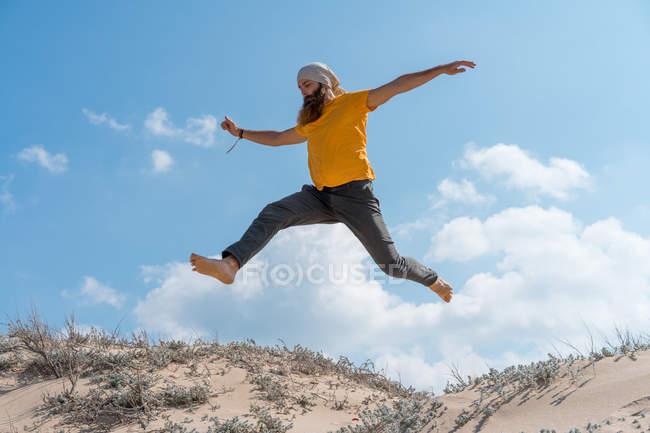 Mann springt auf sandigen Hügel — Stockfoto