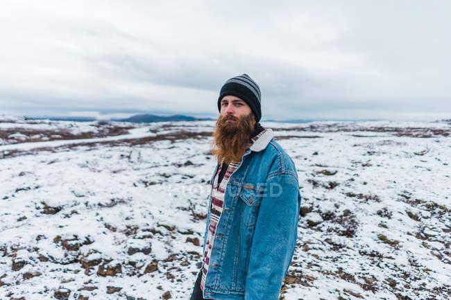 Bearded man walking on snowy field — Stock Photo
