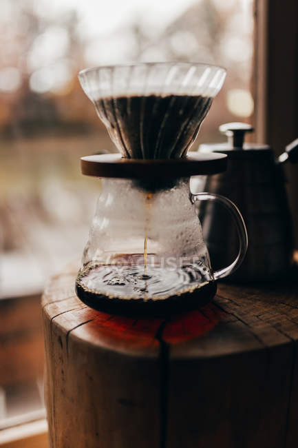 Coffee pouring to glass jug — Stock Photo