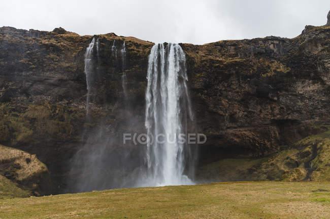 Cachoeira e falésias sob céu tempestuoso — Fotografia de Stock