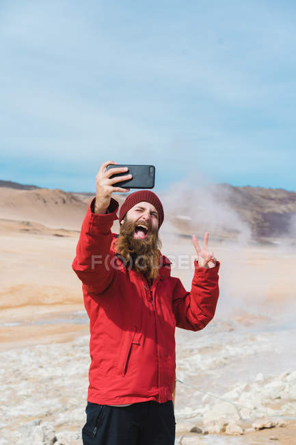 Man standing with smartphone at geyser — Stock Photo