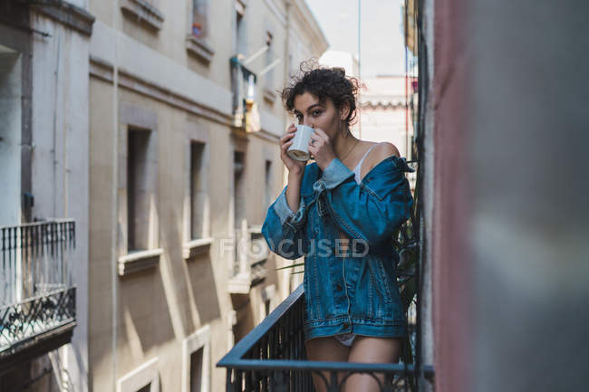 Woman in denim jacket on standing on balcony — Stock Photo