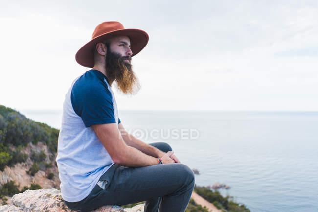 Mann mit Hut sitzt auf Felsen am Meer — Stockfoto