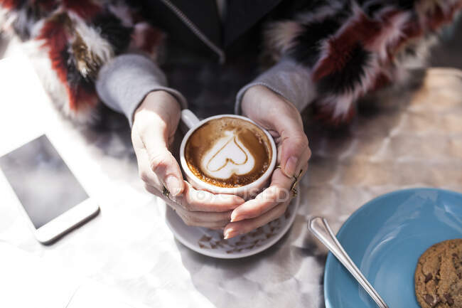 From above hands of unrecognizable woman sitting and holding cup of latte with heart. — Stock Photo