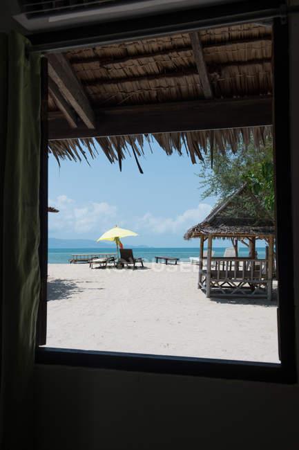 Вікно піщаний пляж з шезлонгами — стокове фото
