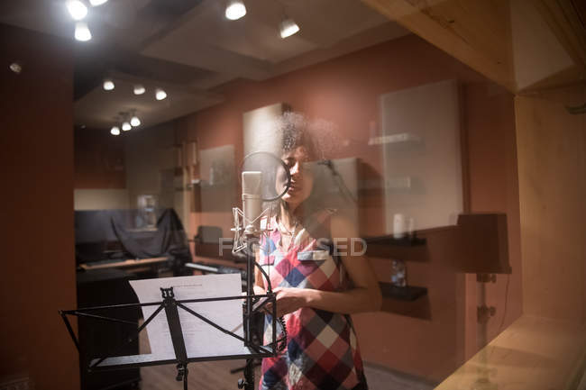 Female vocalist singing in studio — Stock Photo
