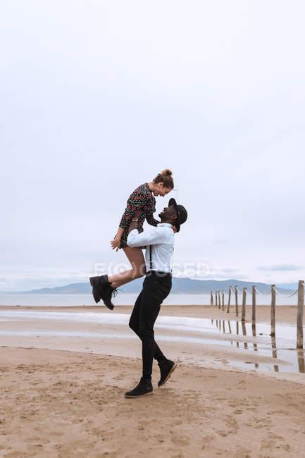 Couple having fun on beach at lake — Stock Photo