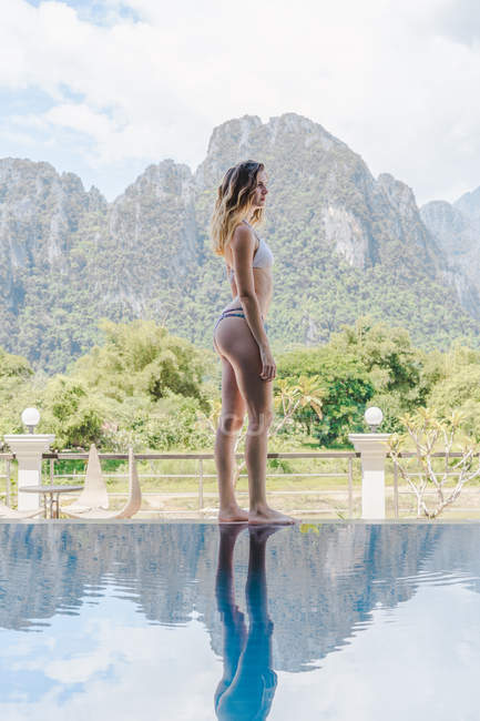 Mujer en bikini de pie junto a la piscina - foto de stock