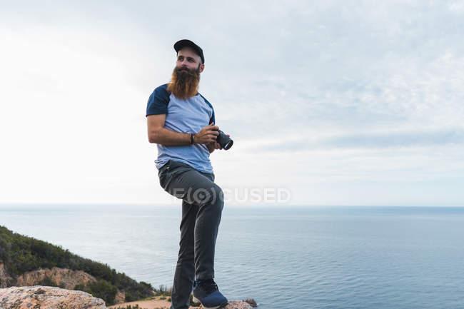 Homem segurando câmera de fotos na costa — Fotografia de Stock