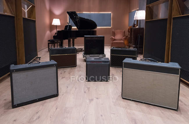 Set of amplifiers near piano — Stock Photo