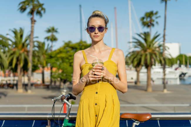 Frau in Sommerkleidung steht mit Fahrrad — Stockfoto