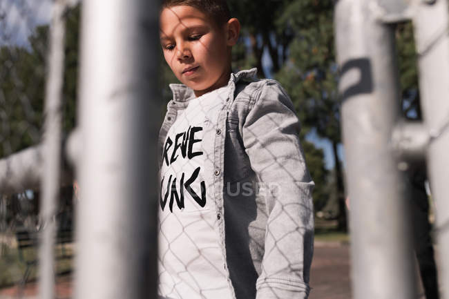 Boy standing at metal fence — Stockfoto