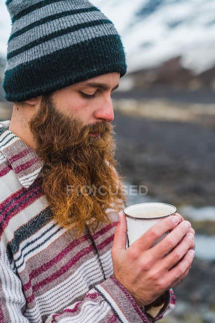 Man holding mug standing in nature — Stock Photo