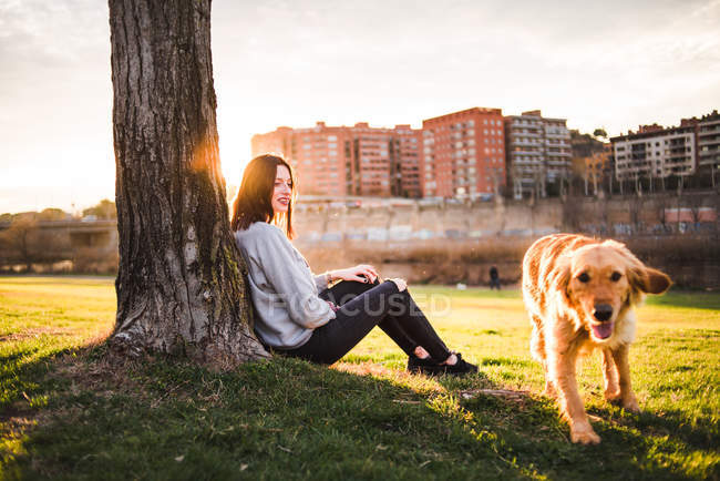 Woman with dog sitting under tree — Stock Photo