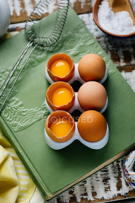Whole and cracked eggs on book — Stock Photo