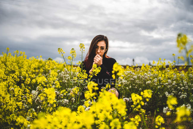 Mujer de pie entre flores amarillas - foto de stock
