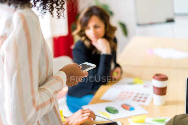 Жінка за допомогою смартфона в конференц-залі — стокове фото
