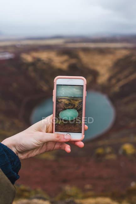 Mão tirando foto de pequeno lago — Fotografia de Stock