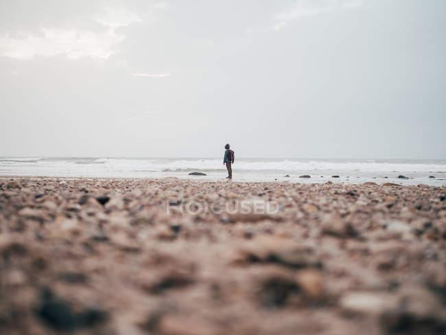 Touriste mâle debout à l'océan calme — Photo de stock