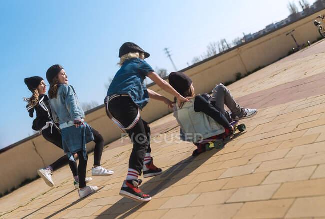 Играть детей на скейтборде на тротуаре — стоковое фото