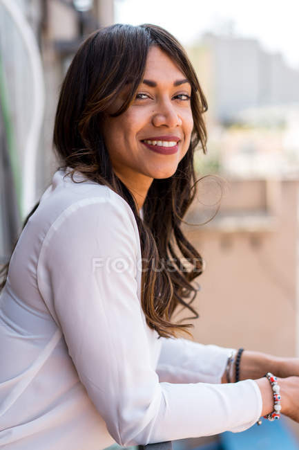 Smiling young woman standing on balcony — Stock Photo