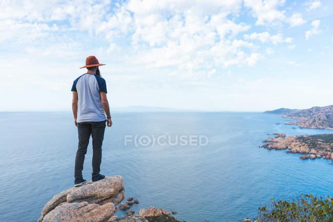 Людина в капелюсі стоячи на скелі на узбережжі — стокове фото