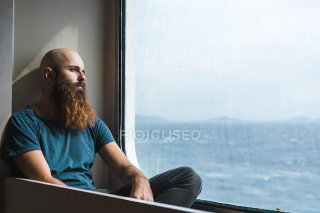 Продуманий людини, що сидить у вікні програми — стокове фото
