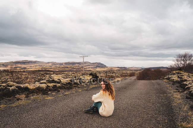 Woman sitting on path in rocky nature — Stock Photo
