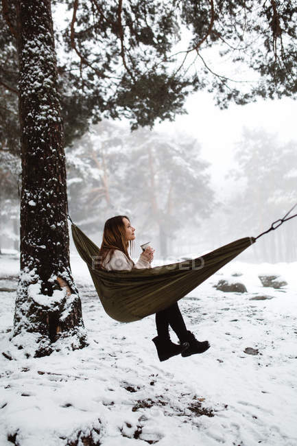 Woman sitting in hammock in winter — Stock Photo