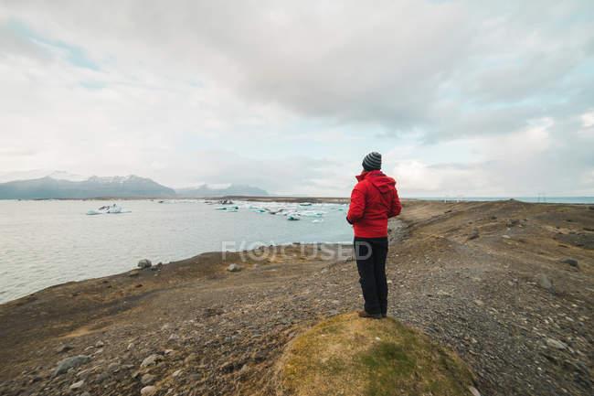 Caminhante em pé no lago e olhando para longe — Fotografia de Stock