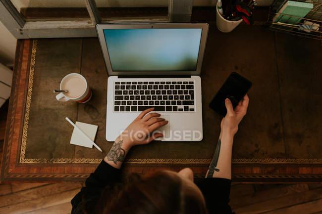 Жінка набравши на ноутбуці та проведення смартфон — стокове фото