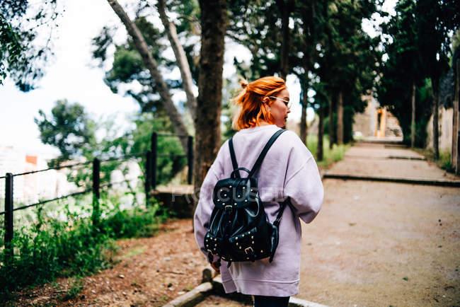 Mulher com mochila andando no parque — Fotografia de Stock