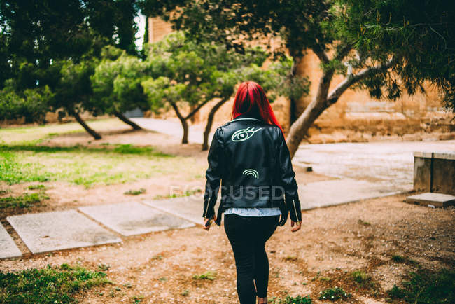 Stylish woman walking on alley — Stock Photo