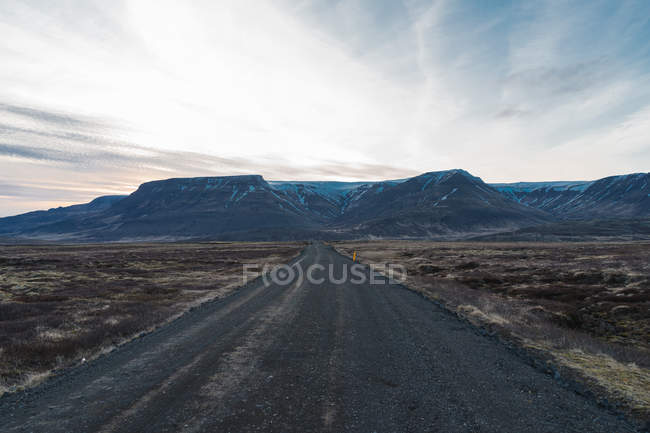 Countryside road towards hills — Stock Photo