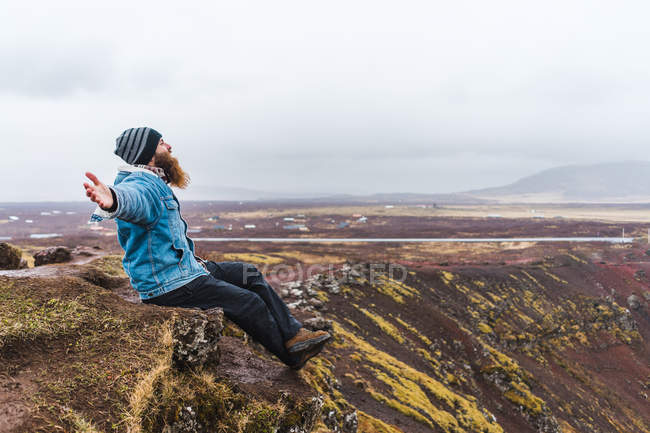 Man sitting in nature with arms outstretched — Stock Photo