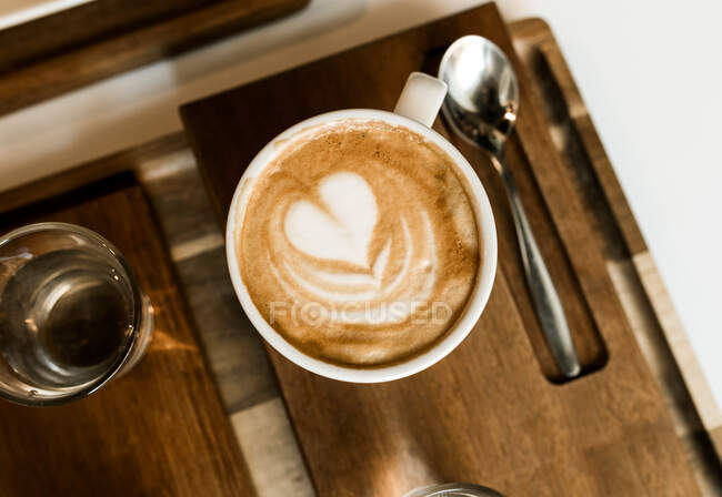 Top view of cup of latte with small heart on wooden board. — Stock Photo