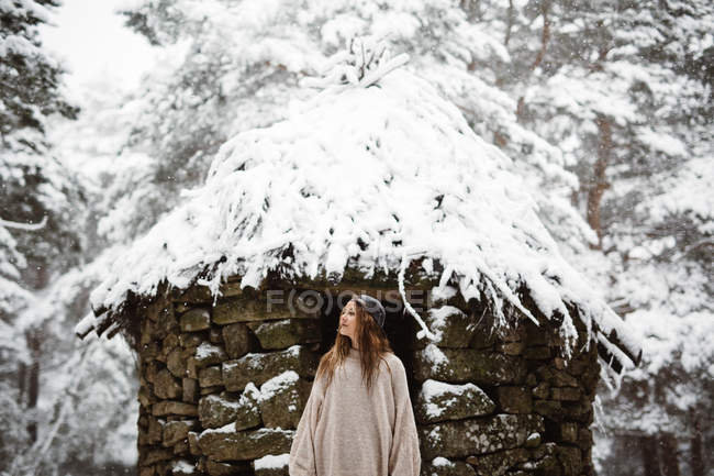 Жінка, стоячи на хатину в зимового лісу — стокове фото