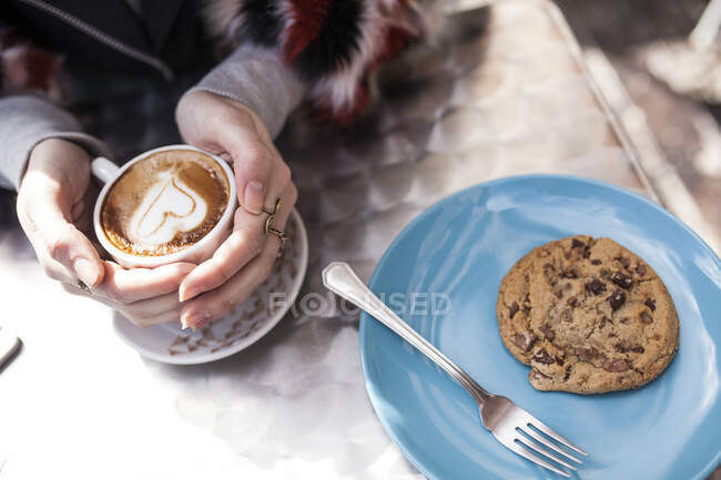 Hands holding cup with heart — Stock Photo
